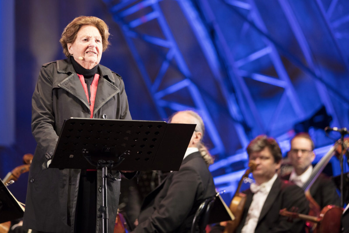 Eine Zeitzeugin spricht auf der Bühne