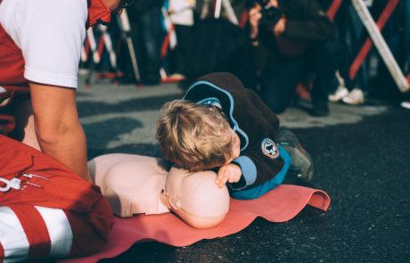 Ein Junge über Wiederbelebung an einer Puppe