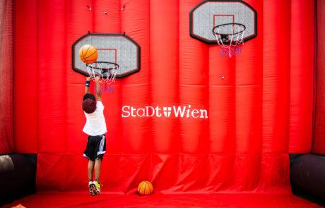 Ein Junge wirft einen Basketball
